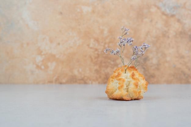 Um cupcake doce inteiro com flor murcha