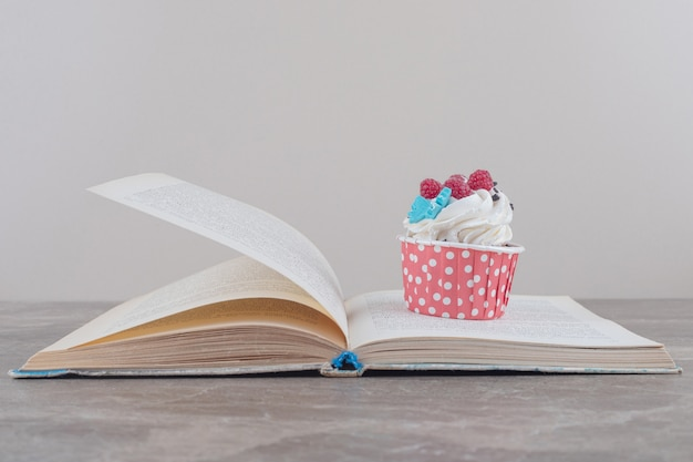 Um cupcake e um livro aberto sobre mármore