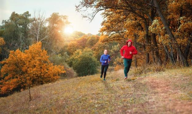 Um cupê de atletas em leggins pretas e jaqueta colorida corre em uma colorida colina de floresta outonal.
