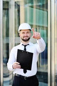 Um, cute, homem jovem, com, um, barba, em, um, camisa branca, e, laço, e, um, branca, construção, capacete
