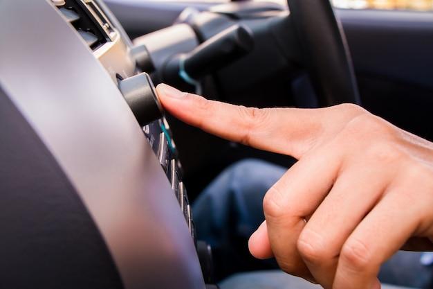 Um dedo do homem aperta o rádio.
