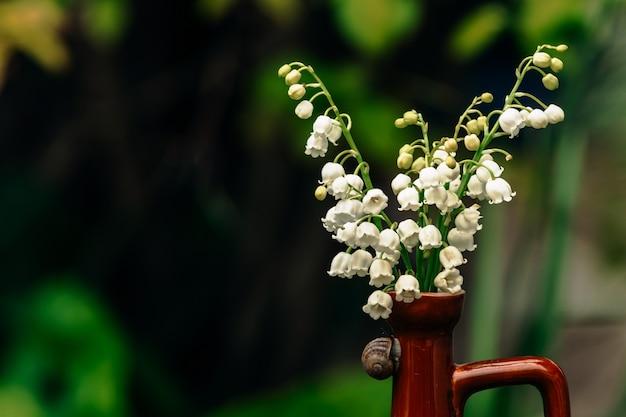 Um delicado buquê de lírios brancos do vale em um pequeno jarro de argila marrom brilhante sobre o qual rasteja um pequeno caracol, apoiado em um velho toco de madeira