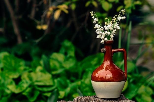 Um delicado buquê de lírios brancos do vale em um pequeno jarro marrom de argila brilhante sobre o qual um pequeno caracol rasteja