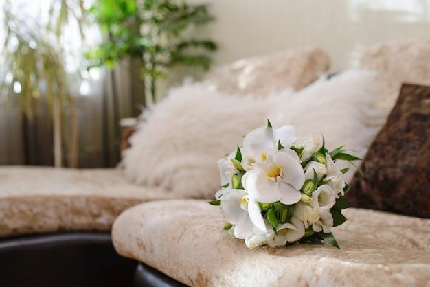 Um delicado e belo bouquet de noiva de orquídeas brancas e rosas vermelhas, deitado no sofá na sala