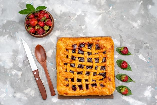 Um delicioso bolo de morango com geléia de morango dentro e morangos frescos no bolo de mesa cinza.