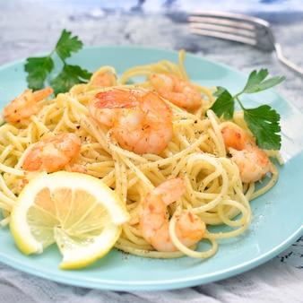 Um delicioso jantar, decorado com salsa e limão. espaguete com camarões em placas azuis.