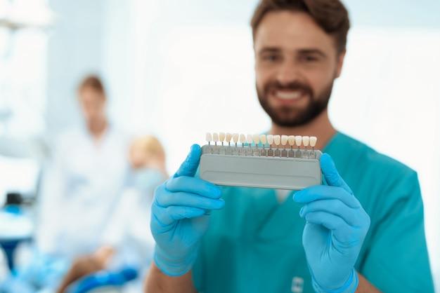 Um dentista está posando com uma escala de cores do dente.