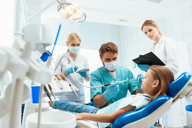 Um dentista está se preparando para tratar os dentes de uma menina
