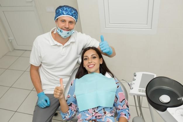 Um dentista masculino novo e um paciente do sexo feminino feliz em um consultório dentista.