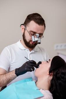 Um dentista masculino se concentra, como ela trabalha na boca de uma menina.