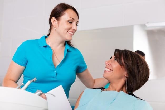 Um dentista termina uma restauração dentária bem-sucedida, um médico aconselha um paciente feliz
