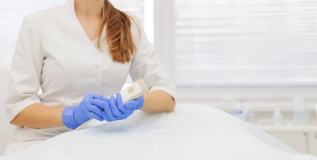 Um dermatologista-cosmologista tem nas mãos uma cavitação especial por ultrassom para a limpeza da pele.