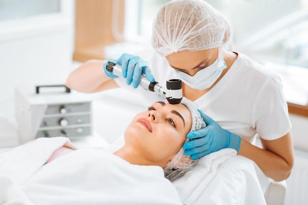 Um dermatologista experiente segurando um dermatoscópio enquanto trabalha com seu paciente