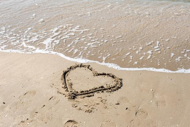 Um desenho de um coração em uma areia amarela em um fundo de bela vista do mar.