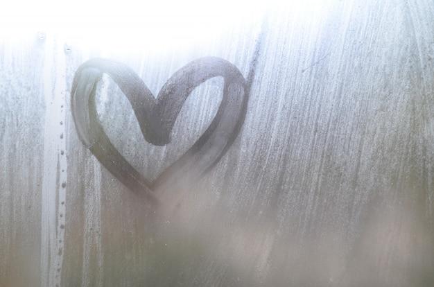 Um desenho em forma de coração desenhado por um dedo em um vidro embaçado em tempo chuvoso
