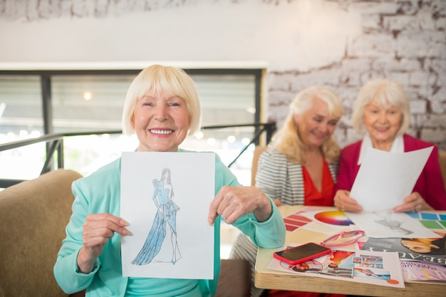Um desenho. uma mulher loira de terno azul mostrando um desenho com um vestido novo