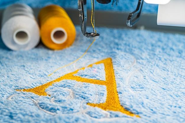 Um design de alfabeto na toalha no aro da máquina de bordar