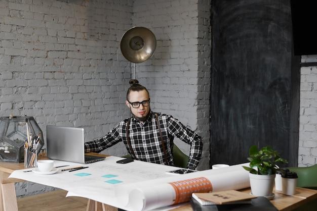 Um designer bonito senta-se à mesa com um laptop e desenhos de engenheiro no interior do loft e lê o novo projeto de edifício social
