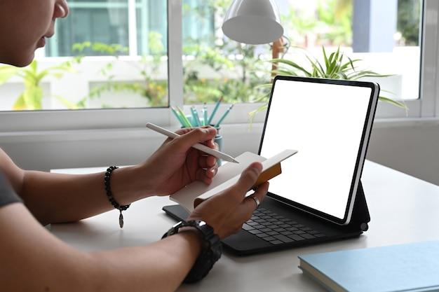 Um designer de mão escreve em seu diário no local de trabalho com o tablet de tela em branco.
