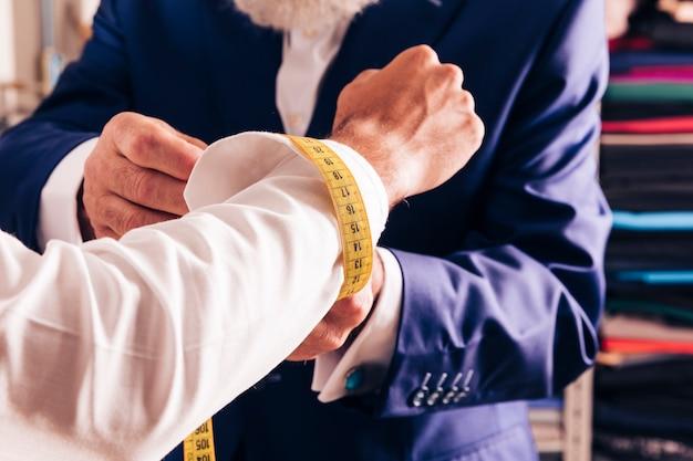 Um designer de moda masculino, tomando a medida de abotoaduras do seu cliente