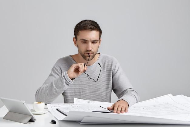 Um designer masculino que trabalha duro tira os óculos e tem uma expressão atenciosa