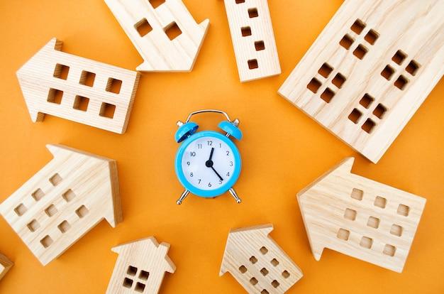 Um despertador azul e muitas casas de madeira em torno do conceito de hipoteca e empréstimo imobiliário e riscos