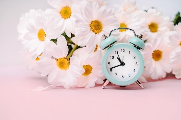 Um despertador azul suave em um buquê de margaridas. conceito floral para férias