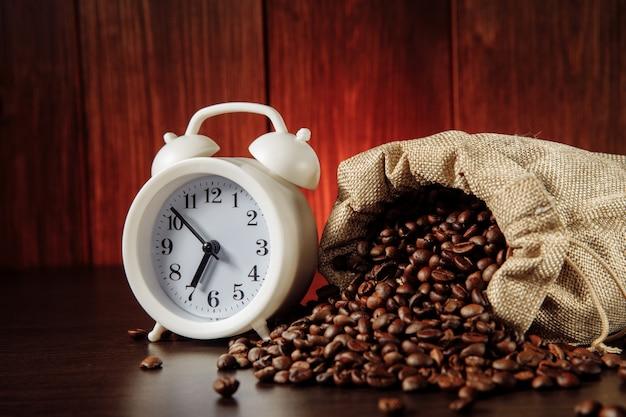 Um despertador branco e grãos de café em uma sacola.