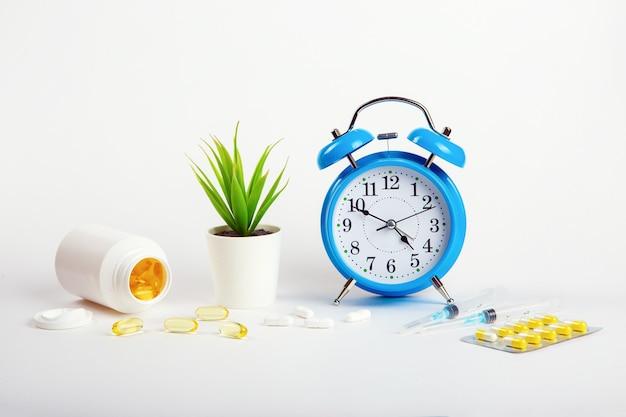 Um despertador fica em uma parede branca que mostra a hora de tomar os medicamentos e, ao lado, seringas e comprimidos médicos.