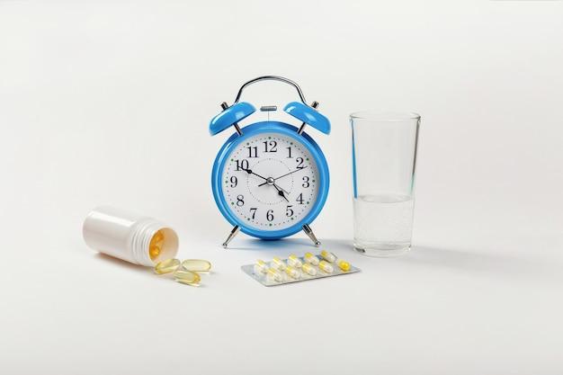 Um despertador mostra a hora de tomar os medicamentos e, ao lado, um copo d'água e pílulas médicas.