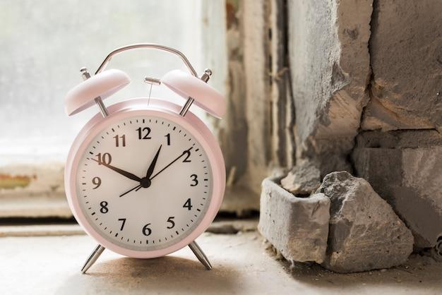 Um despertador no peitoril da janela velho