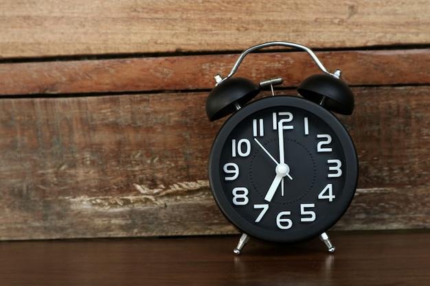 Um despertador preto está na frente do fundo da parede de madeira.