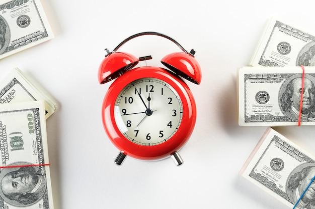 Um despertador retro vermelho brilhante e uma pilha de dólares de papel.