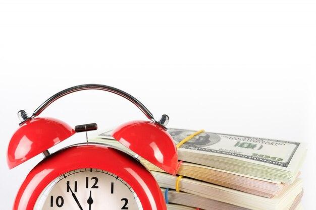 Um despertador retro vermelho brilhante e uma pilha de dólares e euros de papel.