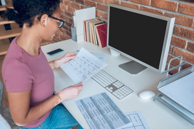 Um dia cheio. uma mulher de óculos trabalhando em um computador e parecendo ocupada