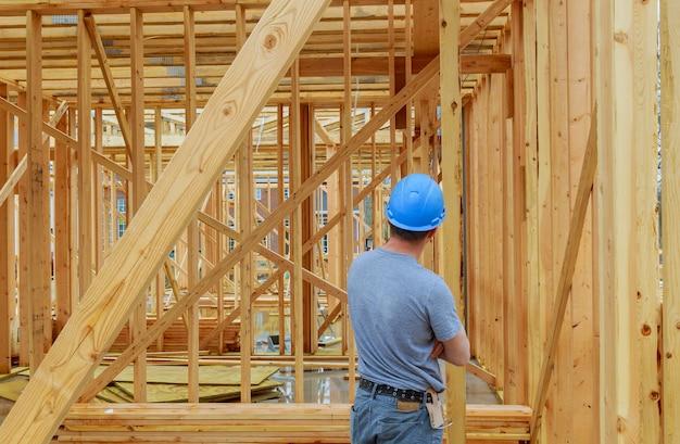 Um dia de construção trabalhador carregando vigas de madeira