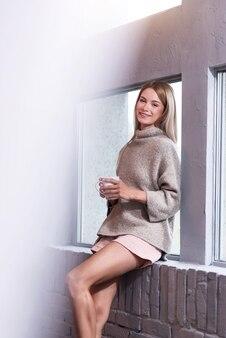 Um dia tão lindo. mulher jovem bonita feliz bebendo café e sorrindo enquanto aprecia a manhã.