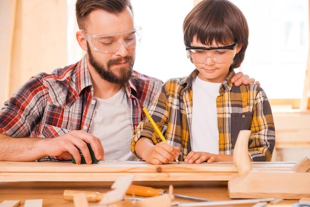 Um dia você será um carpinteiro talentoso. jovem carpinteiro concentrado ensinando seu filho a trabalhar com madeira em sua oficina