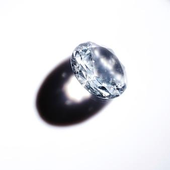 Um diamante de cristal caro com sombra no fundo branco