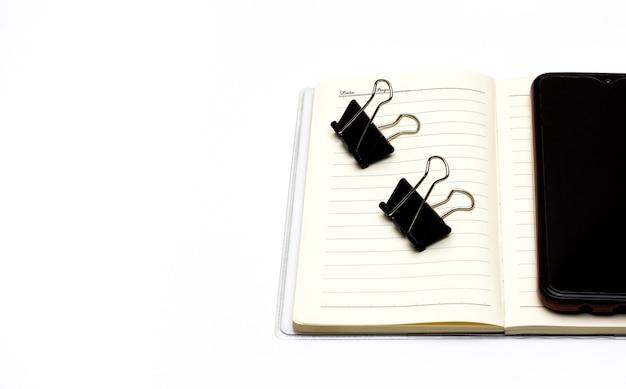 Um diário aberto com um smartphone e clipes de pasta pretos em fundo branco com espaço de cópia