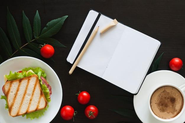 Um diário branco em branco aberto com caneta; tomates; sanduíche e xícara de café sobre fundo preto