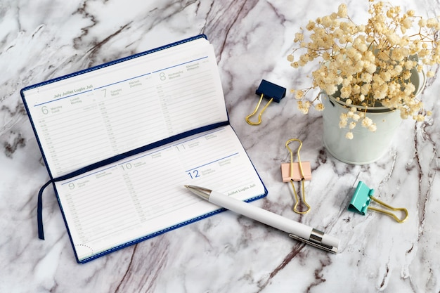 Um diário com uma caneta branca e clipes de papel em uma mesa de mármore e flores brancas. caderno para registros comerciais por uma semana.