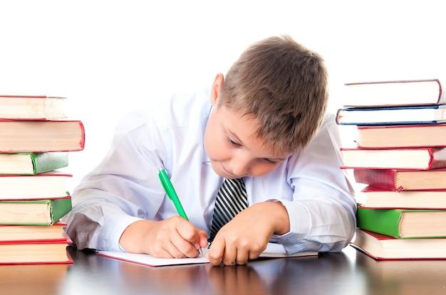 Um diligente estudante do ensino médio senta-se em uma biblioteca com livros e aprende lições, escreve dever de casa