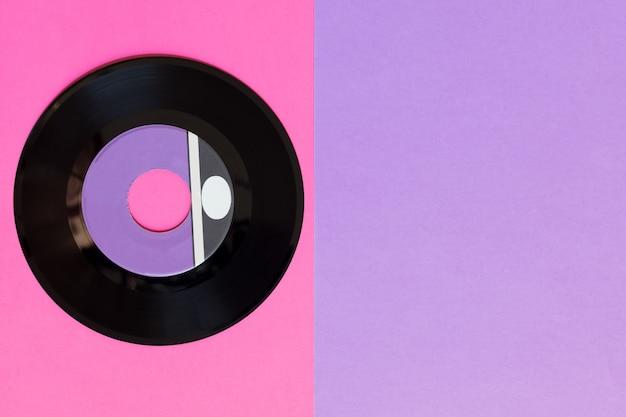 Um disco de vinil desatualizado em um fundo de papel de duas toneladas: rosa e violeta, cultura pop.