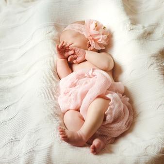 Um doce bebê recém-nascido em rosa dorme, cobrindo seu rosto adormecido