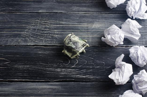 Um dólar amassado em uma mesa ao lado de bolas de papel branco