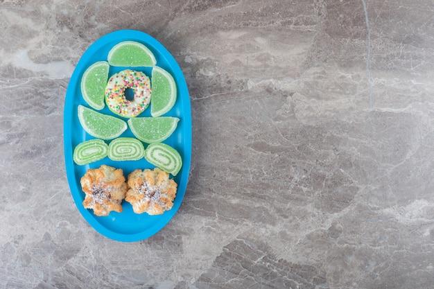 Um donut, biscoitos e marmeladas em uma pequena travessa na superfície de mármore