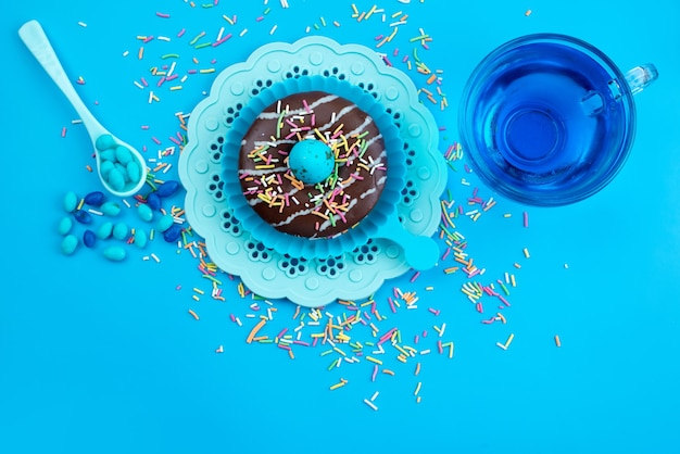 Um donut de chocolate com vista de cima e deliciosos bombons coloridos na mesa azul