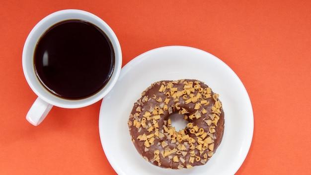 Um donut de chocolate e café americano preto sem leite em uma xícara branca sobre um fundo claro. vista superior, configuração plana. bebida de café fresco ou instantâneo. conceito monocromático.