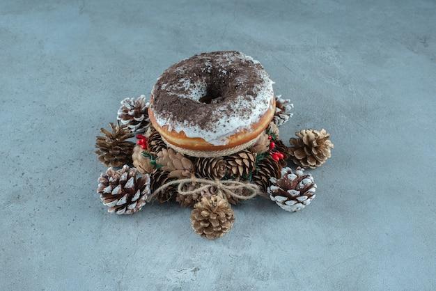 Um donut glaceado aninhado em uma pequena coroa de flores em meio a pinhas na superfície de mármore